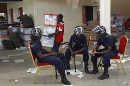 Zambian police sits at the Civic Center in Lusaka, Zambia, as election volunteers carry ballot boxes, September 22, 2011.
