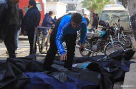 A man attempts to identify bodies after what activists said were airstrikes carried out by the Russian air force in Idlib city, Syria, Dec. 20, 2015.
