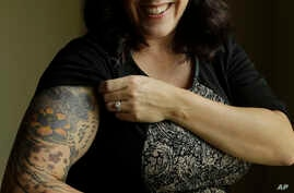 MJ Hegar pulls up her sleeve to reveal part of a tattoo that winds around her arm and back, for a portrait at her home in Round Rock, Texas,, on Aug. 9, 2018.