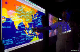 United States Navy lieutenant commander Kirk Benson, points at a map of the South China sea at the Tactical Flag Command Center (TFCC) of the 19,200-ton USS Blue Ridge in Manila, July 22, 2014.