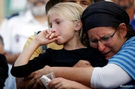 Relatives and friends mourn during the funeral of Hallel Yaffa Ariel, 13, an Israeli girl who was killed in a Palestinian stabbing attack in her home in the West Bank Jewish settlement of Kiryat Arba, at a cemetery in the West Bank city of Hebron, Ju