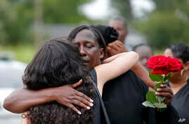 Veda Sterling, aunt of Alton Sterling, hugs a visitor at Alton's burial at the Mount Pilgrim Benevolent Society Cemetery in Baton Rouge, Louisiana, July 15, 2016.
