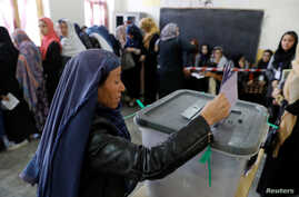 An Afghan woman casts her vote during parliamentary elections at a polling station in Kabul, Afghanistan, Oct. 20, 2018.