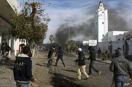 Demonstrators clashing with riot police in a street of Regueb, 09 Jan 2011.