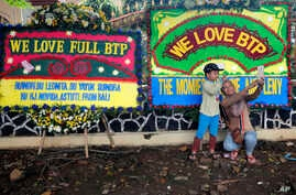 """Supporters of former Jakarta Gov. Basuki """"Ahok"""" Tjahaja Purnama,  take selfie in front of wreaths sent by well-wishers  outside a police prison in Depok, Indonesia, Thursday, Jan. 24, 2019."""