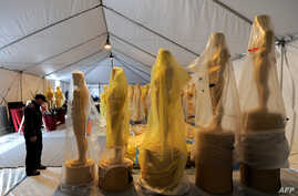 A worker stands next to the Oscar statues during a preparation work for the upcoming OSCARS, the 85th Academy Awards, at Hollywood Boulevard in Hollywood, California, on February 19, 2013. The ceremony is scheduled for February 24, 2013.