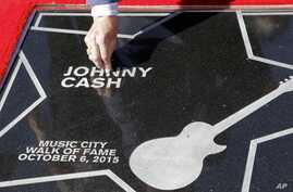 Tommy Cash, the youngest brother of the late Johnny Cash, picks a flower petal off the star presented to Johnny Cash on the Music City Walk of Fame, Oct. 6, 2015, in Nashville, Tennessee.