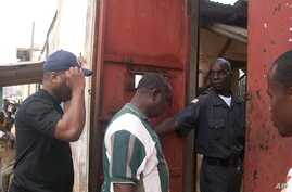 FrontPage Africa editor Rodney Sieh (in back) entering Monrovia Central Prison