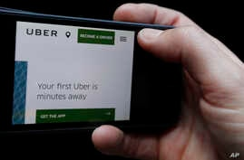 The Uber website is displayed on a phone in London, Sept. 22, 2017.