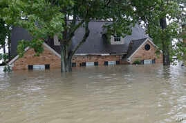 A flooded home is shown as floodwaters from Tropical Storm Harvey rise, Aug. 28, 2017, in Spring, Texas.