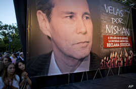 FILE - Women stand beside a poster of late prosecutor Alberto Nisman, marking the first anniversary of his death, in Buenos Aires, Argentina, Jan. 18, 2016.