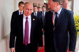 FILE - Russia's President Vladimir Putin, left, and Russian metals magnate Oleg Deripaska, right, attend the APEC Business Advisory Council dialogue in Danang, Vietnam, Nov. 10, 2017.