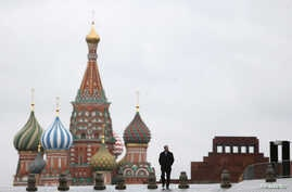 FILE - A man walks along Red Square, with the mausoleum of Soviet state founder Vladimir Lenin, right, and St. Basil's Cathedral seen in the background, in central Moscow, Russia, Dec. 21, 2015.