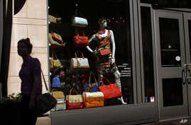 In this April 10, 2013 photo, a woman walks past a retail store's window display in Baltimore.