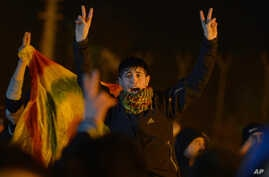 Kurds shout slogans to praise three women activists who were found shot dead in Paris, as ambulances, unseen, carry their coffins at an airport in Diyarbakir, Turkey, January 16, 2013.