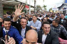 FILE PHOTO: Presidential candidate Jair Bolsonaro is greeted by supporters during an agribusiness fair in Esteio, Rio Grande do Sul state, Brazil Aug. 29, 2018.