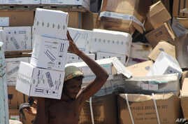 FILE - A Yemeni man unloads medical aid boxes from a boat carrying 460 tonnes of Emirati relief aid that docked in the port of the city of Aden, May 24, 2015.