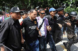 Thai Red Shirt anti-government protest leaders Nattawut Saikuar (2L) and Wiphuthalang (3R, blue cap) are arrested by police officers after they announced to the crowd their surrender on the stage inside the protesters' camp in downtown Bangkok, 19 Ma