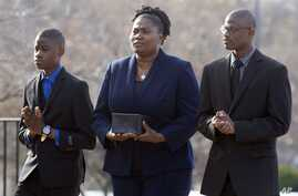Isatu Salia carriers the cremated remains of her husband, Ebola victim Dr. Martin Salia, while their sons Maada Martin Salia, 20, right, and Hinwaii Sakatty Salia, 12, walk with her to enter St. Mary's Church in Landover Hills, Md., for a funeral Mas
