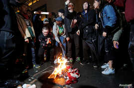 Following President-elect Donald Trump's election victory, protesters burn a U.S. flag outside Trump Tower in New York November 9, 2016.