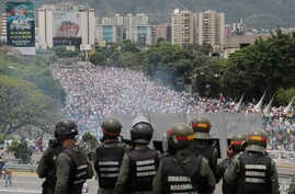 In this May 3, 2017 photo, Bolivarian National Guards stand on a highway overlooking an anti-government march trying to make its way to the National Assembly in Caracas, Venezuela.