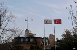 A Cypriot military guard post flies a Greek, left, and Cypriot flags next to a Turkish military guard post with Turkish, right, and Turkish Cypriot breakaway flags, between UN buffer zone, in Nicosia, Cyprus, Jan. 17, 2017.