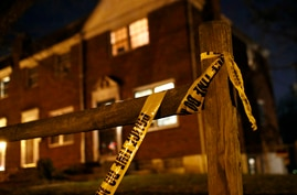 FILE - Crime scene tape that was left behind at the scene of a homicide clings to a fence post in Baltimore, Dec. 21, 2017 photo.