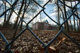 FILE - A fence encloses an estate in the village of Upper Brookville in the town of Oyster Bay, N.Y., on Long Island.