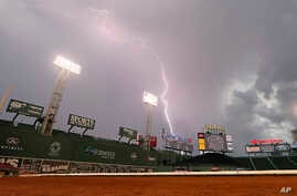 FILE - Lightning strikes over Fenway Park in Boston delay a baseball game between the Boston Red Sox and the Toronto Blue Jays, Sept. 6, 2014.