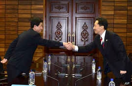 In this photo released by South Korean Unification Ministry, head of South Korean working-level delegation Lee Duk-haeng, right, shakes hands with his North Korean counterpart Park Yong Il during their meeting at Tongilgak in the North Korean side of