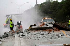 FILE - Construction crews work on a section of Interstate 20 West that buckled in Decatur, Georgia, April 17, 2017.