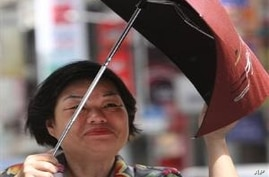 A Taiwanese woman holds her umbrella tight against powerful gusts of wind generated by typhoon Nanmadol in Taipei, Taiwan, Monday, Aug. 29, 2011. Typhoon Nanmadol has slammed into Taiwan, closing schools, workplaces and government offices. It has dum