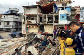 People survey a site damaged by an earthquake, in Kathmandu, Nepal, April 25, 2015.