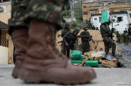 Brazilian soldiers and Civil Policemen carry drugs seized in the woods of Chatuba slum during an operation against drug dealers in Rio de Janeiro, Brazil, Aug. 22, 2018.