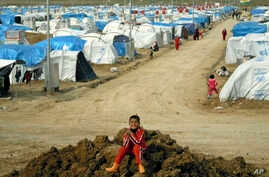 FILE - A Syrian Kurdish refugee plays on a pile of dirt in the Dumiz refugee camp in northern Iraq, Feb. 15, 2013.