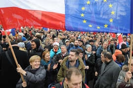Protesters wave Polish and European Union flags during an anti-government demonstration in Warsaw, Poland, Dec. 19, 2015.