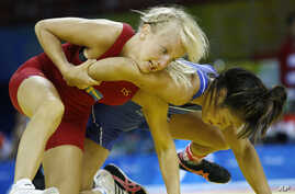 Clarissa Chun of the U.S., in blue, wrestles Sweden's Sofia Mattsson in their women's freestyle 48 kilogram match at the Beijing 2008 Olympics in Beijing, China, Aug. 16, 2008.