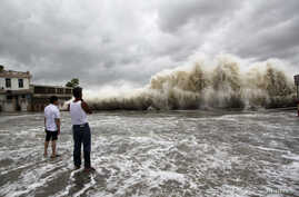People watch waves hit the shores as Typhoon Usagi approaches in Shantou, Guangdong province, September 22, 2013. China's National Meteorological Center issued its highest alert, warning that Usagi would bring gales and downpours to southern coastal