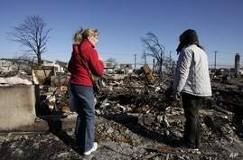 Cathy O'Hanlon, left, looks at the charred remains of her home with a friend in Breezy Point, Queens borough, New York, Nov. 14, 2012.