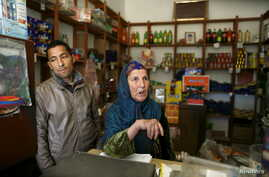 Nasser Abaidi (L), 34, an unemployed graduate, looks on while his mother speaks with journalists inside her shop in the impoverished Zhor neighborhood of Kasserine, where young people have been demonstrating for jobs.