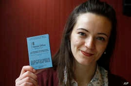 Dora-Olivia Vicol from Romania shows her UK residence documentation during and interview with Associated Press in London, March 8, 2017.