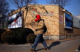 A man walks by the Canadian Embassy in Beijing, Dec. 14, 2018.