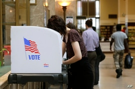 People cast their votes at a polling station inside the Enoch Pratt Free Library's central library branch in Baltimore, April 26, 2016.