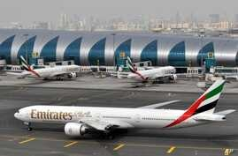 An Emirates plane taxis to a gate at Dubai International Airport at Dubai International Airport in Dubai, United Arab Emirates. Emirates Airline, the world's biggest international air carrier by traffic, said Wednesday it is cutting flights to five U