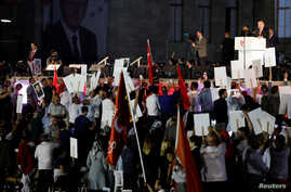 FILE - Turkey's President Recep Tayyip Erdogan addresses his supporters during a ceremony marking the first anniversary of the attempted coup in front of the Turkish Parliament in Ankara, July 16, 2017.