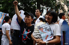 FILE - Tran Thi Nga, right, holds her son and an anti-China poster as she takes part in a rally in Hanoi, July 8, 2012.