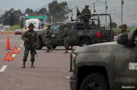 "Soldiers stand guard at a checkpoint near Contepec, in Michoacan state,  after Mexico's most notorious drug lord, Joaquin ""El Chapo"" Guzman, broke out of a high-security prison Saturday for the second time, escaping in a tunnel built right under his"