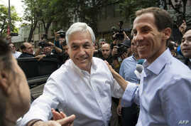 FILE - Chilean former President Sebastian Pinera (L) and Chilean right-wing lawyer and Santiago's mayoral candidate Felipe Alessandri greet supporters during Municipal elections in Santiago, Oct. 23, 2016.