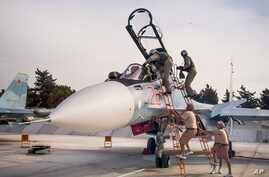 FILE - Russian air force pilots assisted by ground crew climb into their fighter jet at Hemeimeem airbase, Syria.