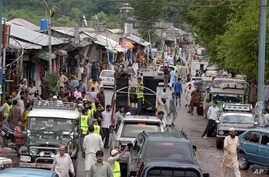 A convey carrying doctors, medicines and activists a charity group Falah-e-Insaniat Foundation pass through main bazaar of Chakothi near Line of Control along the Indian border, some 61 kilometers (38 miles) from Muzaffarabad, Pakistan on Aug. 2, 201